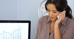 Casual Hispanic business woman talking on mobile phone in office Stock Photos