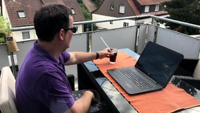 Casual homeoffice on the balcony. Casual homeoffice: A middle aged man is entering his balcony in very casual clothing carrying a softdrink, briefly opening his stock footage