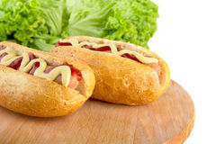 Casual hotdogs on round cutting board with salad on white Stock Photos