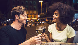Casual interracial couple drinking wine during date.  Royalty Free Stock Images