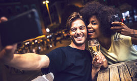 Casual interracial couple drinking wine during date and taking a. Selfie in a terrace Stock Photography