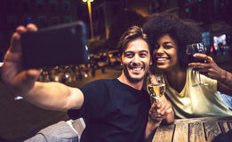 Casual interracial couple drinking wine during date and taking a. Selfie in a terrace Stock Images