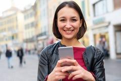 Casual joven feliz del estudiante vestido usando el teléfono en la ciudad urbana Foto de archivo libre de regalías