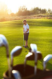 Casual kid at a golf field holding golf club Royalty Free Stock Image