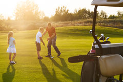 Casual kids at a golf field holding golf clubs studing with trai. Ner. Sunset Royalty Free Stock Photography