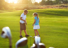 Casual kids at a golf field holding golf clubs. Sunset Royalty Free Stock Images