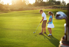 Casual kids at a golf field holding golf clubs. Sunset Stock Image
