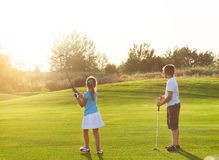 Casual kids at a golf field holding golf clubs. Sunset Stock Photo