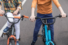 Casual kids riding bicycles on the street. Cropped shot of casual kids riding bicycles on the street Royalty Free Stock Photos