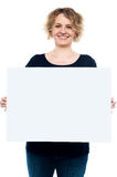 Casual lady displaying blank white billboard Royalty Free Stock Image