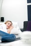 Casual lazy young woman sleeping on a bed Stock Photography