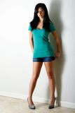Casual look. Model poses wearing t-shirt and shorts with back to wall Royalty Free Stock Images