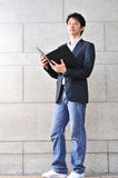 Casual Looking Asian Man reading Stock Images
