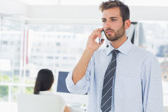 Casual male artist using mobile phone with colleague in the background Royalty Free Stock Images