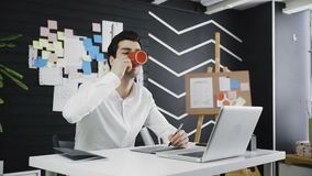 Casual male designer drinking coffee and using graphics tablet in a modern office stock video