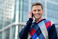 Casual male executive talking via mobile phone Royalty Free Stock Image