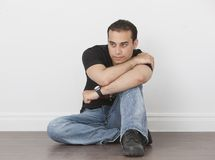 Casual Male in Jeans and T-Shirt. Leaning against white wall Royalty Free Stock Photo
