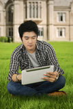Casual male student with tablet at park. Photo of male college student sitting on the park while using a digital tablet Royalty Free Stock Photos