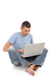 Casual male working on laptop computer. Handsome young male working on laptop computer. isolated Royalty Free Stock Photography