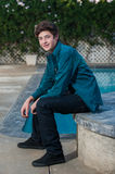 Casual male youth in relaxed pose. Handsome Latino teen smiling while seated near edge of pool Royalty Free Stock Photo
