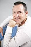 Casual man. A portrait of a casual clean cut man with hand under chin on a gray background Stock Photography