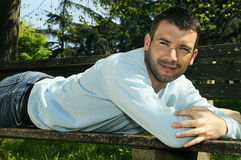 Casual man. Attractivz man is relaxing on a bench in a natural environement stock image