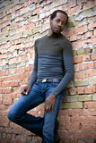 Casual Man of African Decent. Handsome young adult male stands with back resting against a rough brick wall.  Man is wearing casual street clothes and has a slim Stock Photos