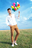 Casual man with balloons and hand in pocket Royalty Free Stock Photos