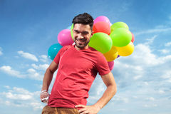 Casual man with balloons and hands on hips Stock Photos