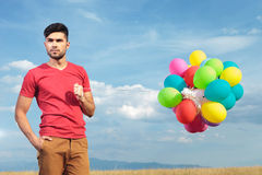 Casual man with balloons holds hand in pocket Stock Images