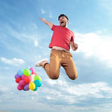 Casual man with balloons jumps in the air Stock Photography
