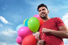 Casual man with balloons looks away Stock Image