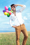 Casual man with balloons looks far away Royalty Free Stock Photos
