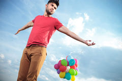 Casual man with balloons looks to his side Stock Photo