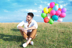 Casual man with balloons sits on grass and smiles Stock Image
