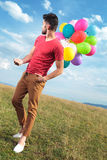 Casual man with baloons looks back Stock Images