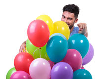 Casual man behind a bunch of baloons is pointing finger Royalty Free Stock Photos