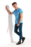 Casual man in blue polo shirt, leaning against studio wall Stock Photo