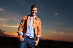 Casual man with both thumbs in pockets and sunset behind Royalty Free Stock Photo