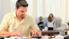 Casual man calculating his bills with his family in the background Stock Photo