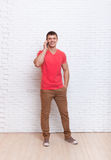 Casual Man Cell Phone Call Speak Smartphone Stand Over Wall. Casual Man Cell Phone Call Speak Smartphone Full Length Over White Brick Wall Stock Image