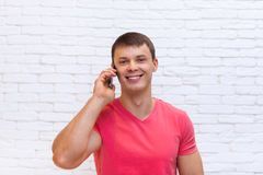 Casual Man Cell Phone Call Speak Smartphone Standing Over Wall. Casual Man Cell Phone Call Speak Smartphone Smile Over White Brick Wall Stock Image