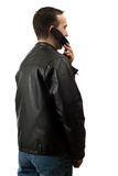 Casual Man On Cellphone. A young man wearing a leather jacket is facing away from the camera and talking on his cellphone, isolated against a white background Stock Photos