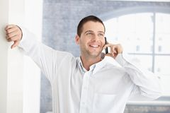 Casual man chatting on mobile smiling Royalty Free Stock Image