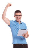 Casual man cheers with tablet in hand Stock Photos
