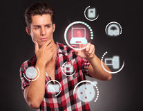 Casual man choosing from different media types Royalty Free Stock Image