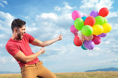 Casual man with colorful balloons Stock Image