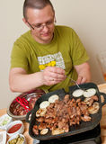 Casual man cooking meat. Man inside cooking meat and onions on a portable grill Stock Photo