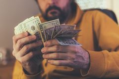 Casual man is counting american dollar banknotes royalty free stock photography