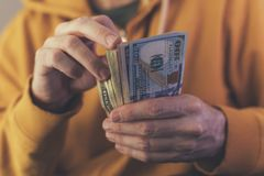 Casual man is counting american dollar banknotes stock photography